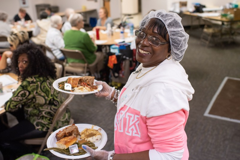 volunteer holds two plates of food, smiles for the camera