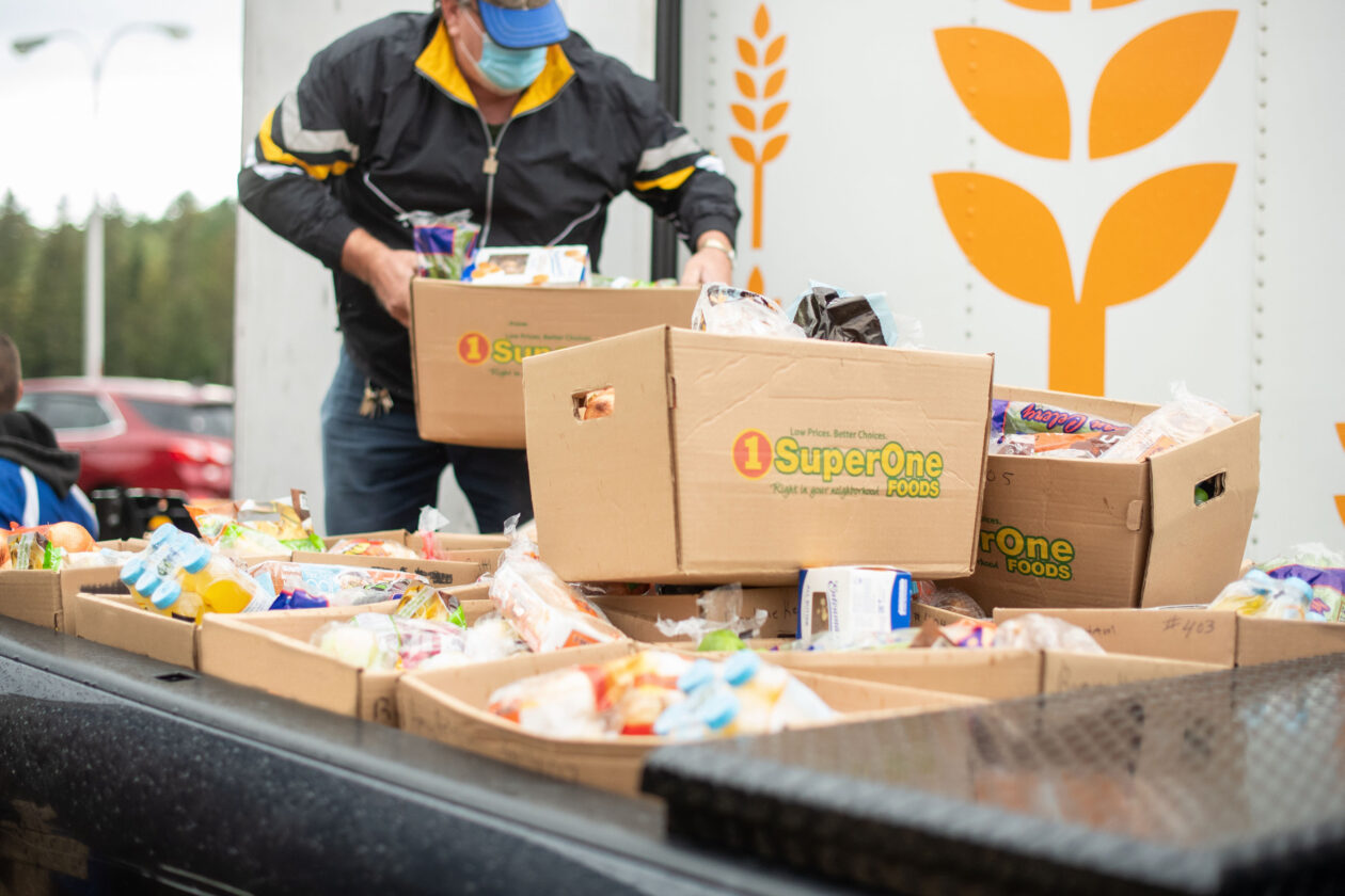 man loads boxes of food into truck
