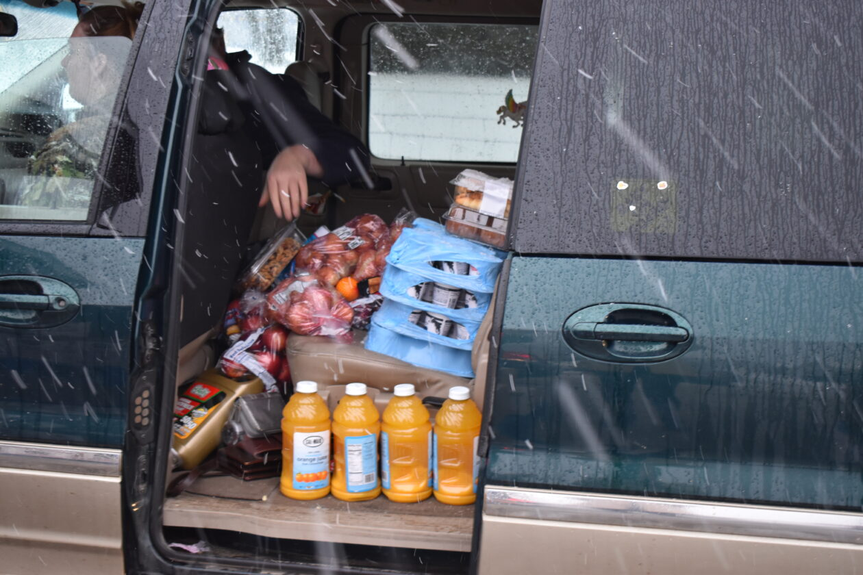 A neighbor's car is loaded with a variety of fresh produce and other food.