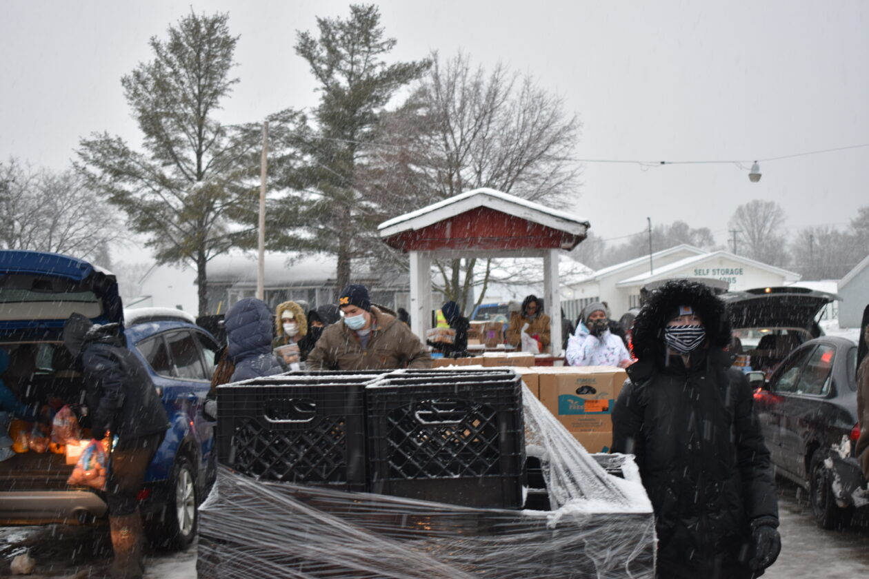 Volunteers load cars with food amid a snowy backdrop