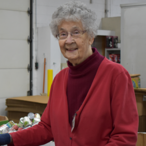 Mary poses while volunteering at the food bank