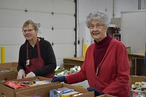 Mary and another volunteer sort food at Feeding America West Michigan