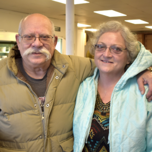 John and Lynn, an older couple, pose at the pantry