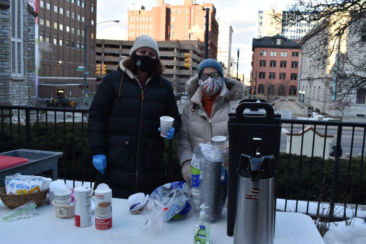 Two volunteers serve coffee at St. Mark's breakfast program