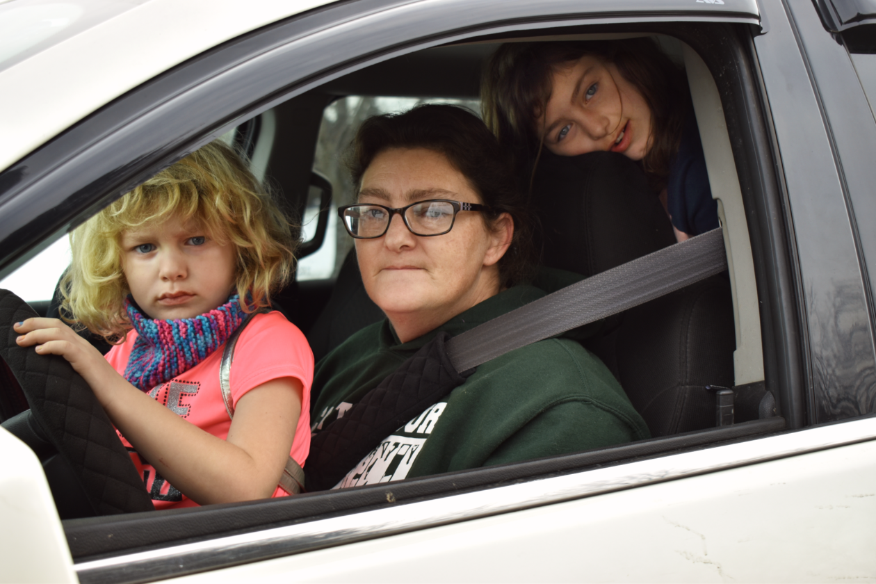Amanda and her daughters peer out of their car