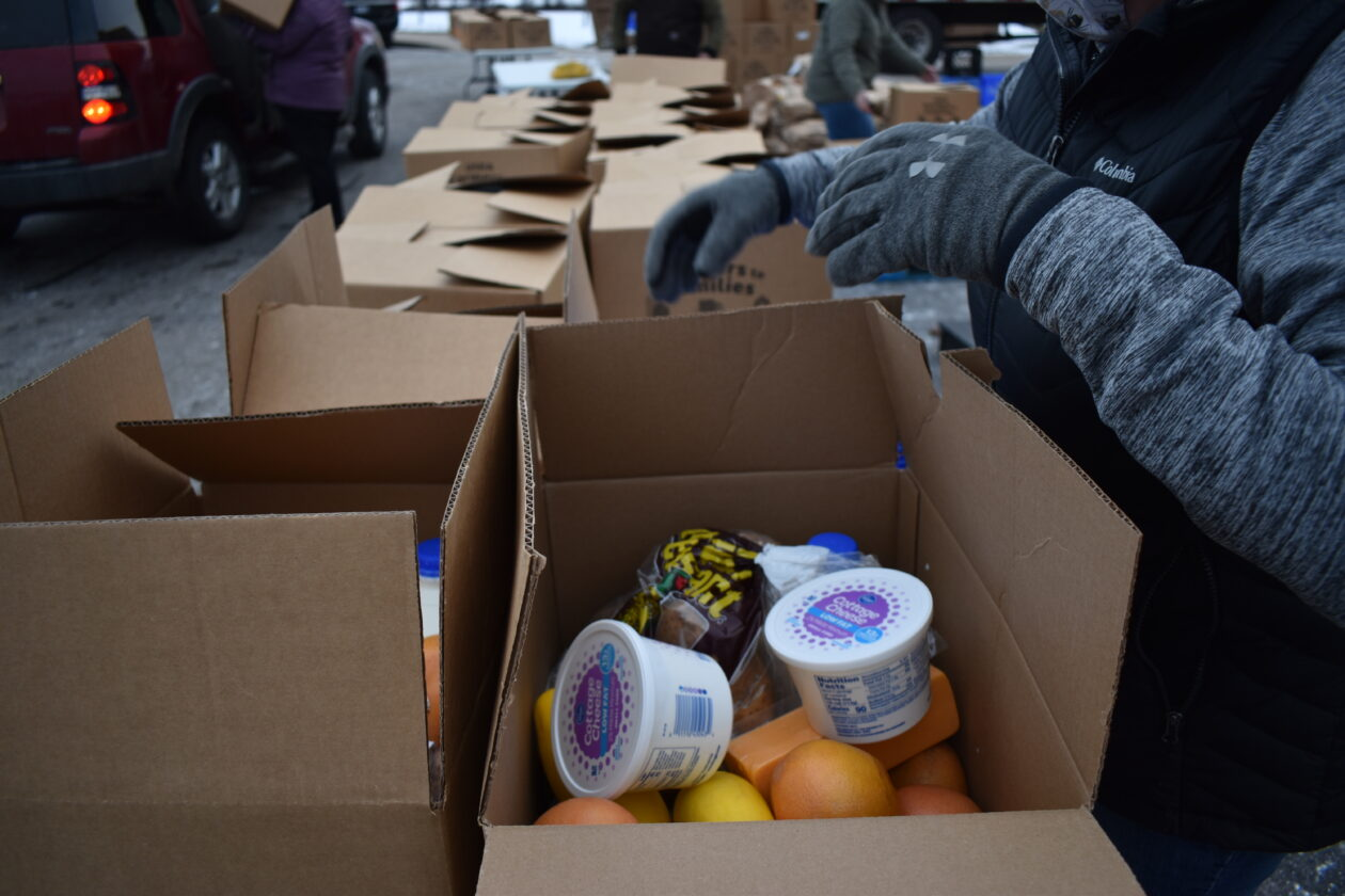 A box of cottage cheese, oranges, bread and more is sorted by a volunteer