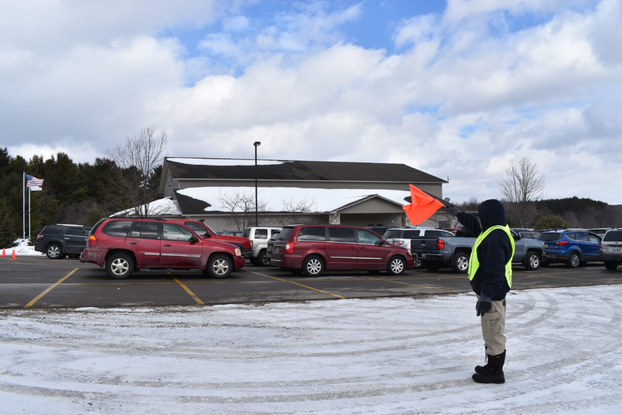 A Mobile Pantry volunteer waves a flag at a line of cars