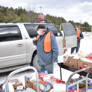 A volunteer loads a truck with food