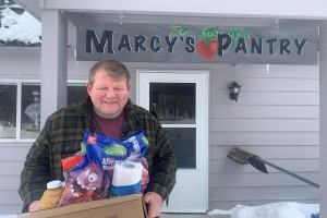 A senior man carries a box of food. He's in front of a sign that says Marcy's Pantry. There's a strawberry on the sign.