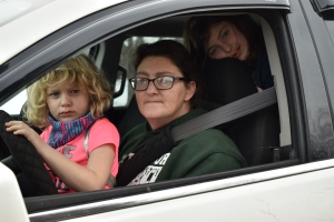 A mom and her two daughters sit in a car