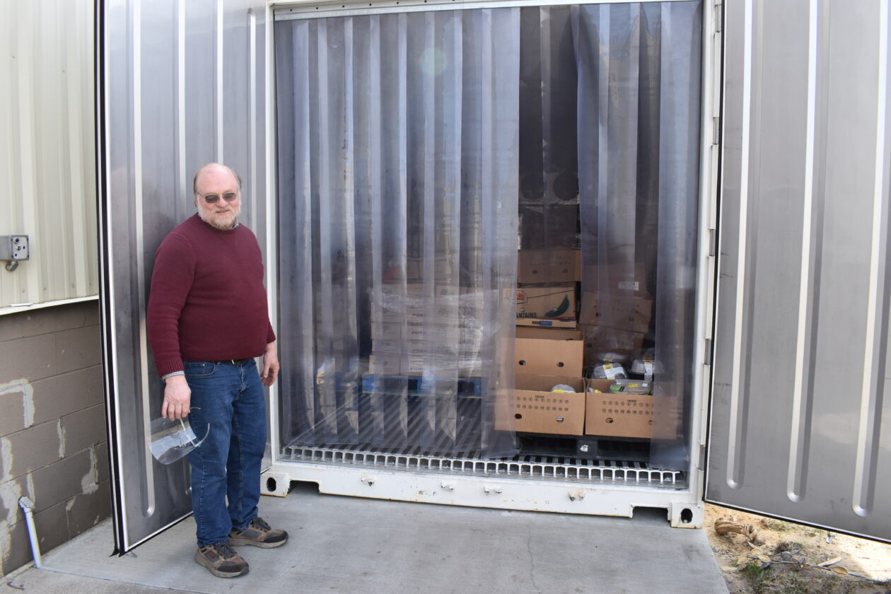 Rich poses in front of his new freezer, a large shipping container.