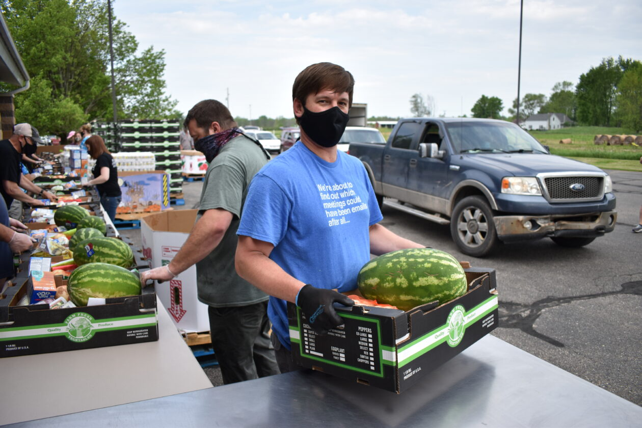 masked man holding box of food at Mobile Pantry