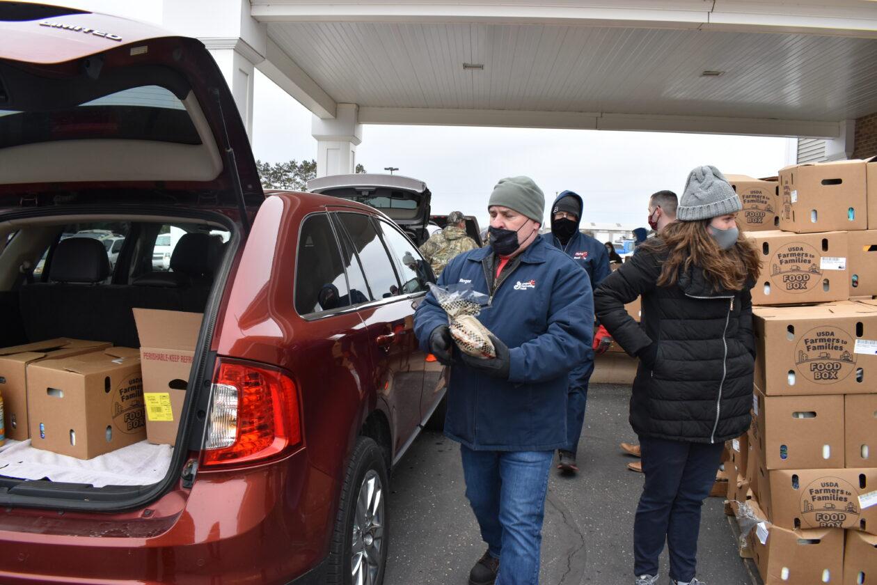 A Yoplait volunteer helps load a car with food