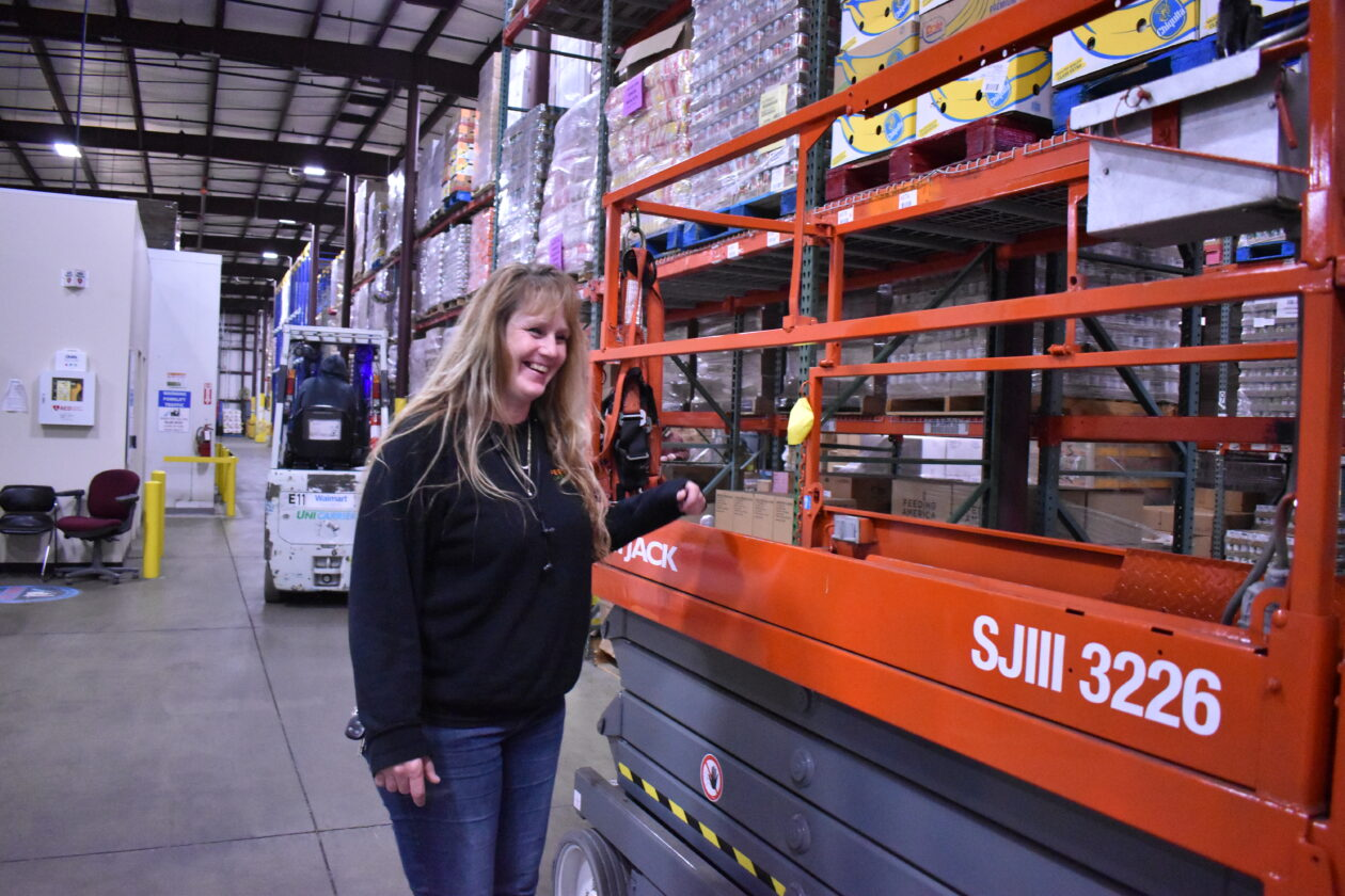 Leslie stands with the scissor lift with racks full of food behind her.
