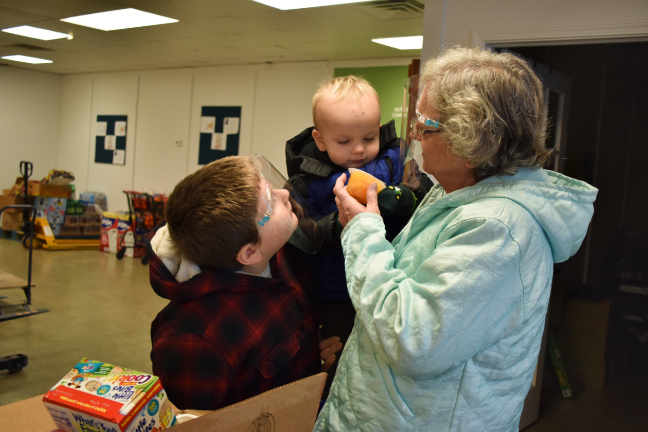 A grandma and her two grandkids look at food they've received
