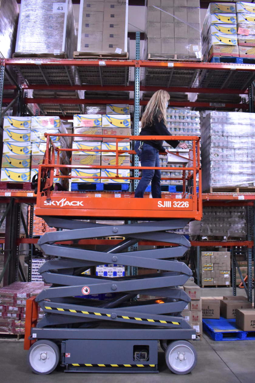 Leslie demonstrates the scissor lift, which has a caged platform to stand on and an accordion to push it up high.