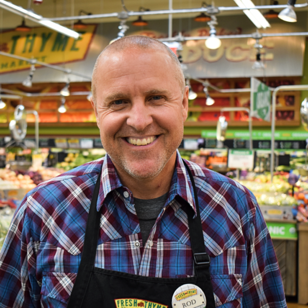 Rod smiles while standing inside his store. He's wearing an apron and lots of fresh food is behind him.