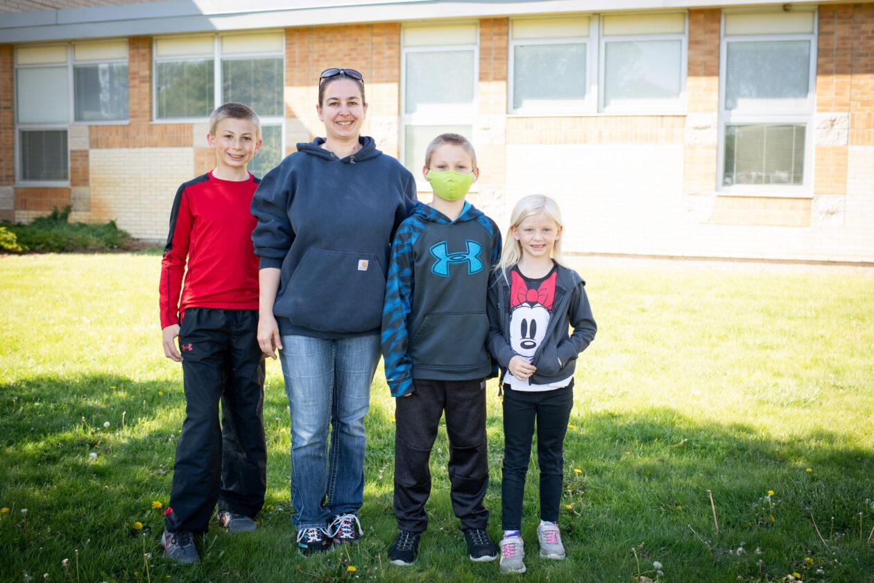 April stands with her three children in front of the school