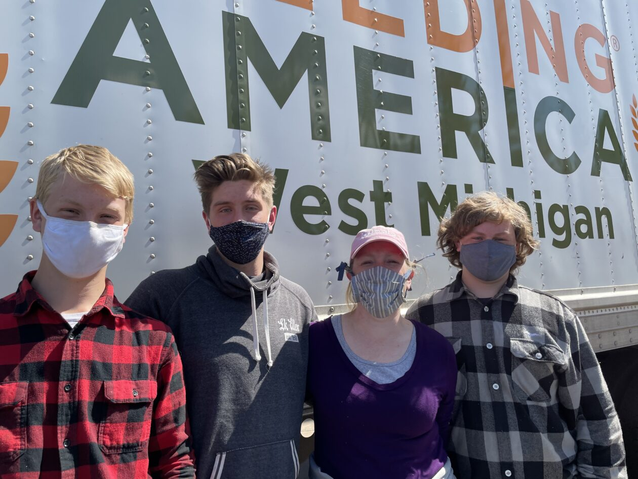 Justina poses with her three sons at a Mobile Pantry