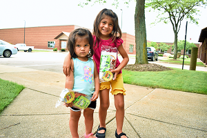 Two sisters stand outdoors holding their prepackaged meals