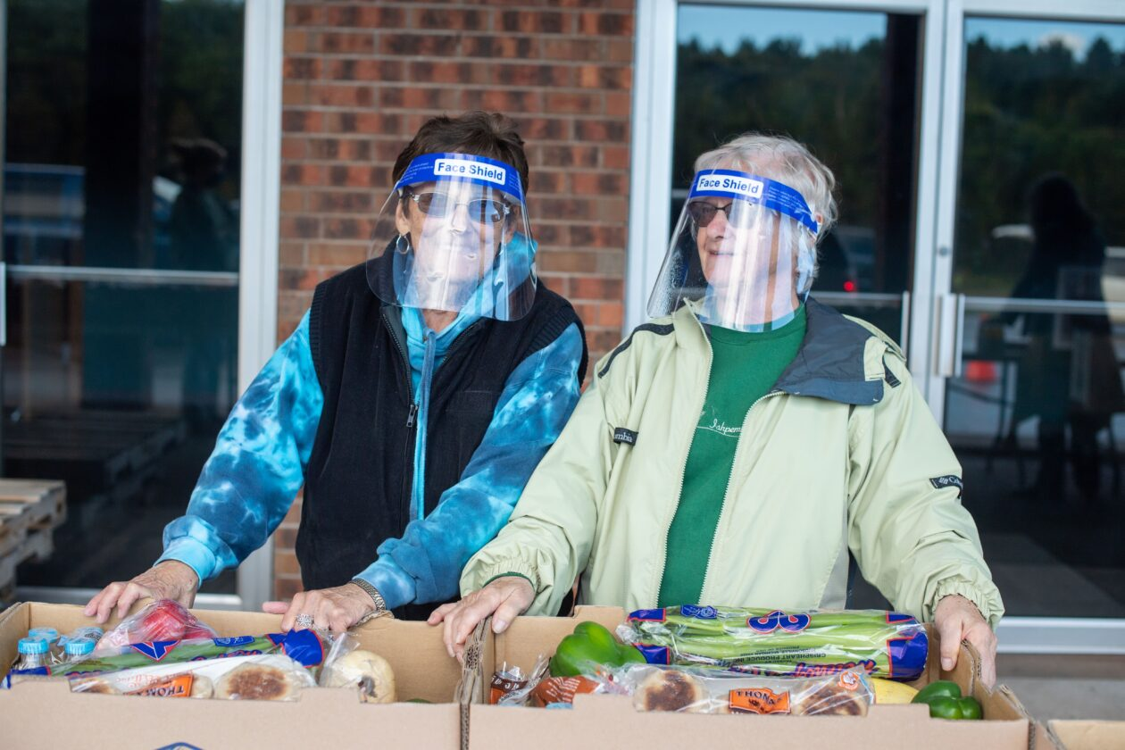 Two women stand behind a row of boxes of food at a Mobile Pantry
