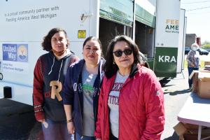 Three women (grandma, daughter, granddaughter) pose in front of a mobile pantry truck