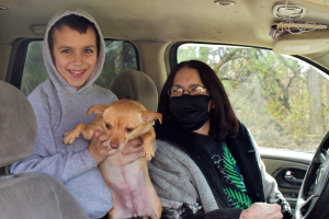 A grandma sits with her great-grandson in a car. He holds up their chihuahua