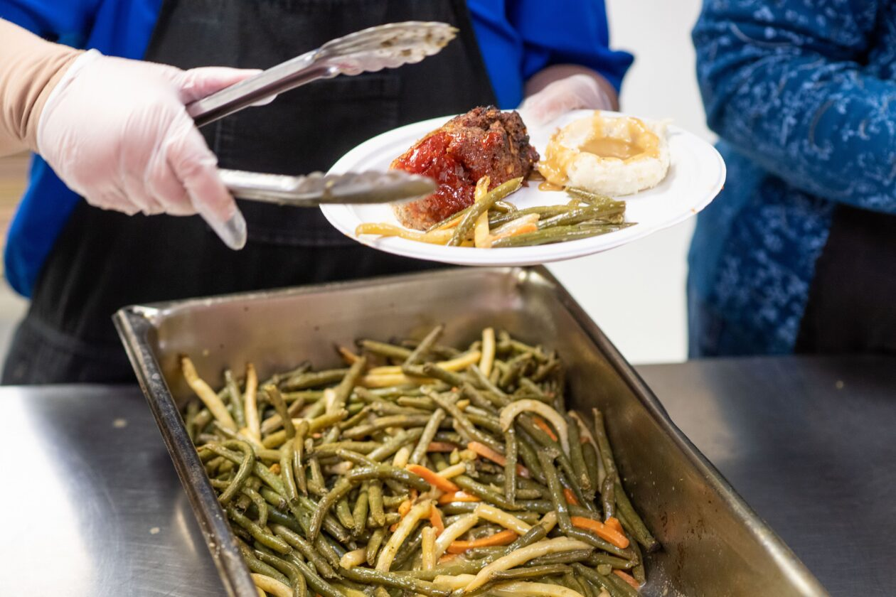 Meatloaf and greenbeans are scooped onto a plate at a food bank agency partner.