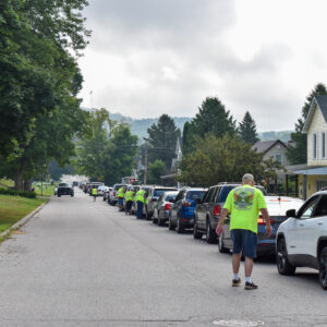 Cars line up on a neighborhood street as volunteers sign them in.