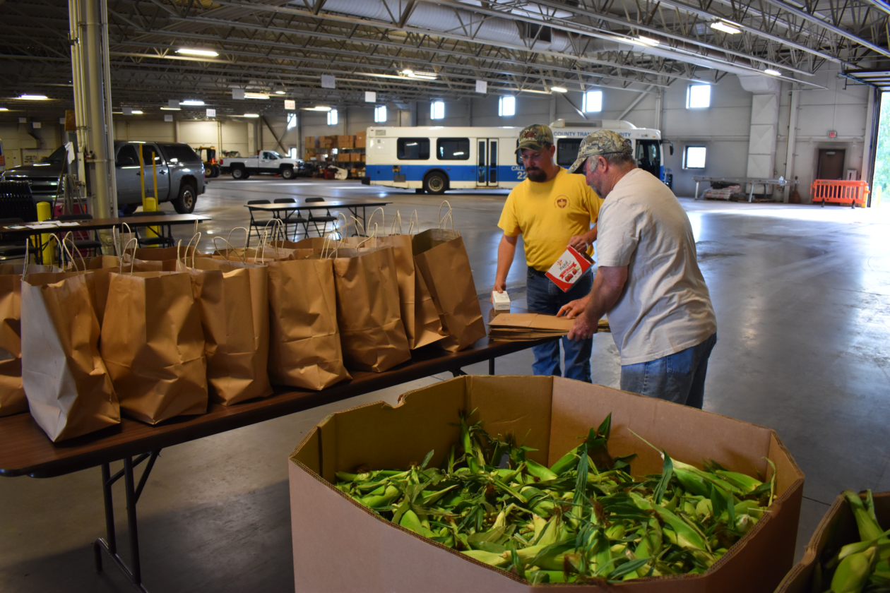 Two volunteers stand near brown bags and a gaylord full of corn.