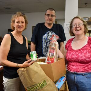 Food pantry volunteer Kathy stands with Yasna and Billy around a cart of food