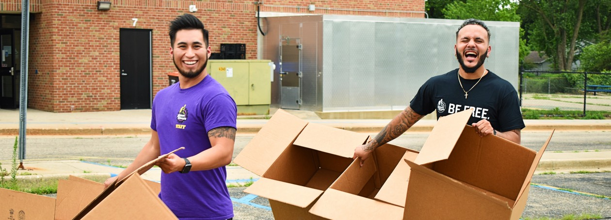 Happy Planet Fitness employees carrying empty boxes